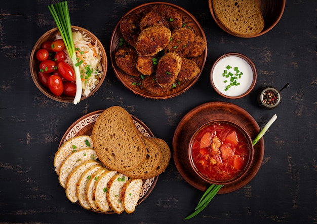 Traditionele oekraïense russische borsjt of rode soep met sappige heerlijke vleeskoteletten