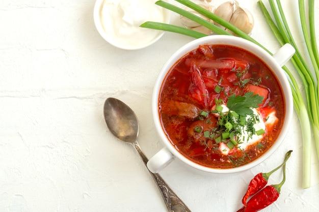Traditionele oekraïense russische soep (borscht) van biet met greens en zure room.