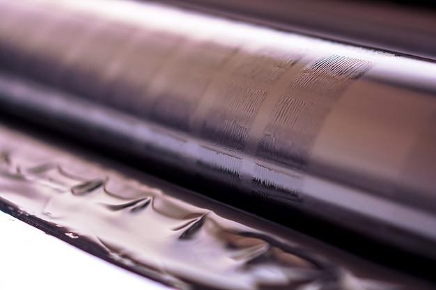 Traditionele offsetpers. afdrukken in inkt met cmyk, cyaan, magenta, geel en zwart. grafische kunst, offsetdruk. detail van drukrol in offsetmachine van vier zwarte inktlichamen