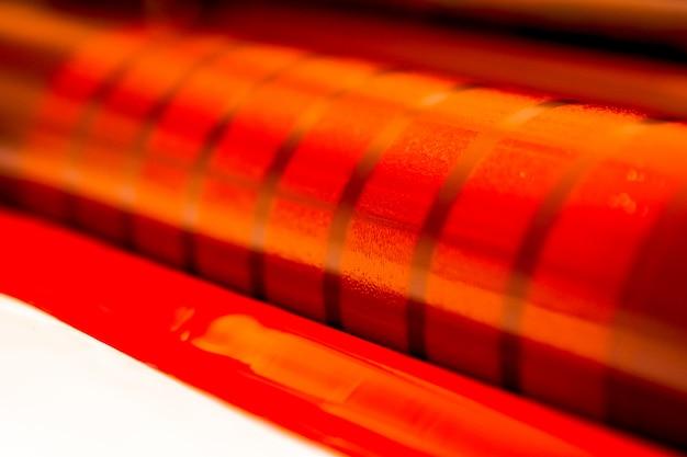Traditionele offsetpers. afdrukken in inkt met cmyk, cyaan, magenta, geel en zwart. grafische kunst, offsetdruk. detail van een drukrol in een offsetmachine met vier lichamen van magenta inkt