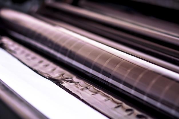 Traditionele offsetpers. afdrukken in inkt met cmyk, cyaan, magenta, geel en zwart. grafische kunst, offsetdruk. offsetdrukrol met vier zwarte inktlichamen