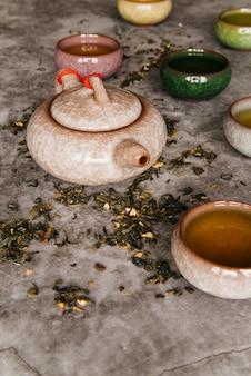 Traditionele oostelijke theepot en theekopjes op concrete achtergrond