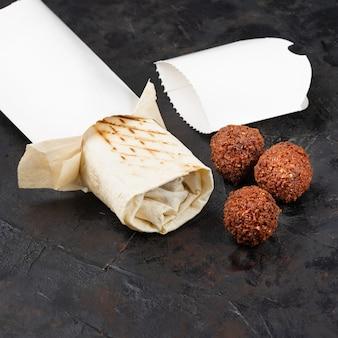 Traditionele oosterse shoarma met gebakken falafel koteletten op een zwarte achtergrond. gezonde tussendoortjes of afhaallunch. concept van eco-pakketten voor recyclebare materialen. kopieer ruimte