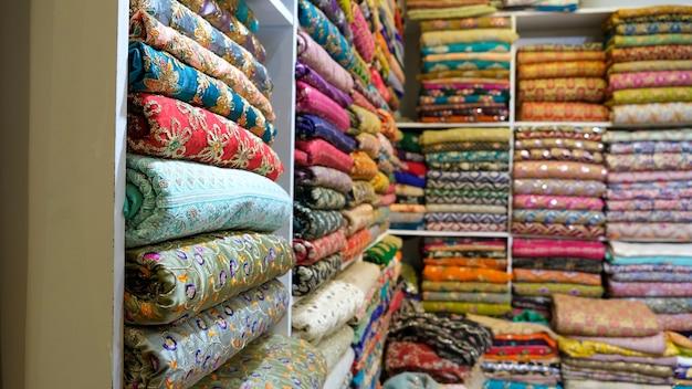 Traditionele oosterse veelkleurige stoffen gestapeld in de winkel