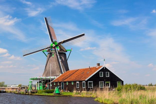 Traditionele oude nederlandse windmolen met huis blauwe hemel in het dorp van zaanse schans, nederland.