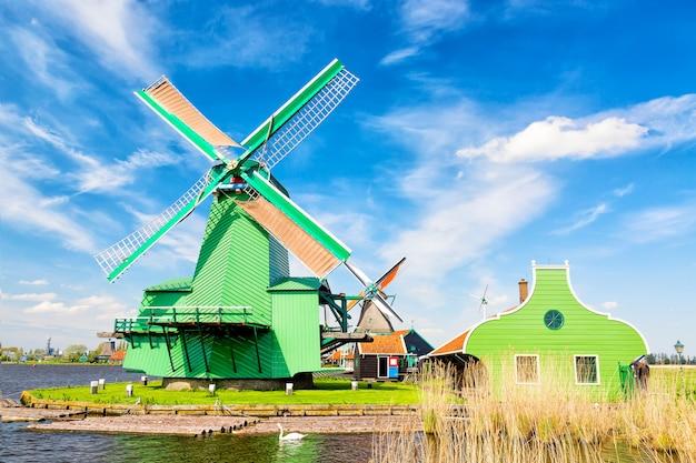 Traditionele oude nederlandse windmolens met huis en zwaan tegen blauwe hemel in het dorp van zaanse schans, nederland