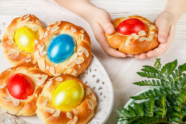 Traditionele pasen-broodjes versierd met eieren, amandelbloemblaadjes en citroenschil in kinderhanden