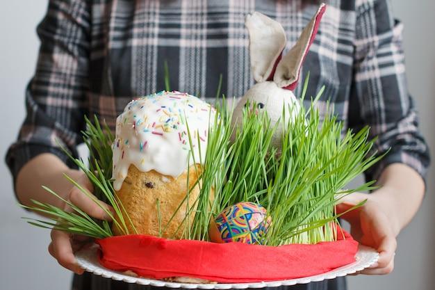 Traditionele pasen-cake, eieren en konijntje in het gras in de handen van de vrouw.