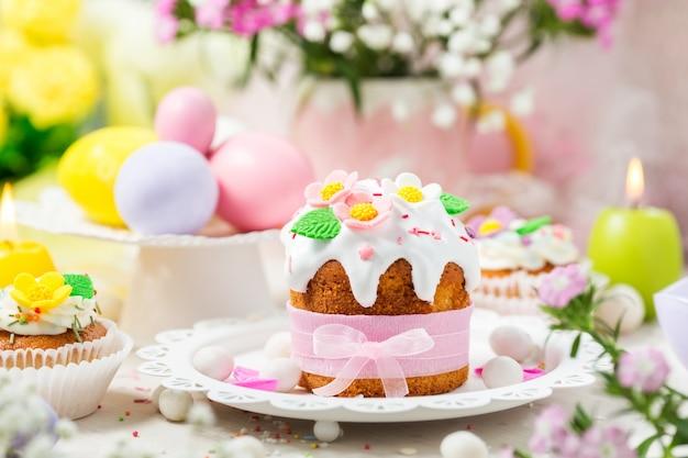 Traditionele pasen-cake met witte suikerglazuur verfraaide suikerbloemen en kleurrijke eieren.