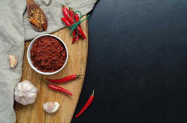 Traditionele pasta met hete chilisaus maghreb, harissa op een donkere leisteenachtergrond, tunesische keuken, arabische, mexicaanse keuken, adjika, muhammara. horizontale oriëntatie met plaats voor tekst