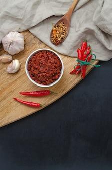 Traditionele pasta met hete chilisaus maghreb, harissa op een donkere leisteenachtergrond, tunesische keuken, arabische, mexicaanse keuken, adjika, muhammara. verticale oriëntatie met plaats voor tekst