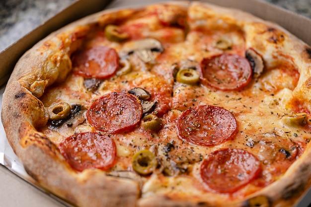 Traditionele pepperonispizza in document vakje. snel voedselconcept