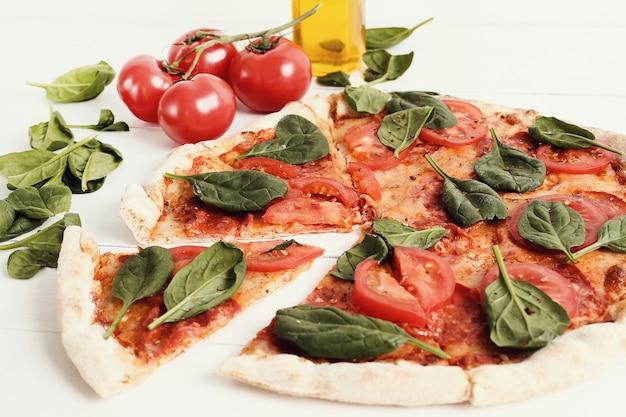 Traditionele pizza met plakjes tomaat en basilicumblaadjes