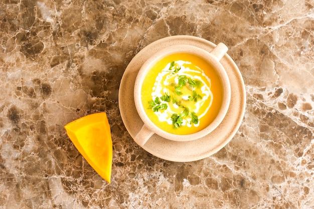 Traditionele pompoensoep in een soepbord met pompoenpitten en gehakte peterselie. marmeren achtergrond. bovenaanzicht.