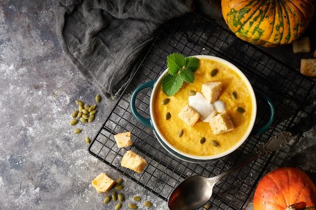 Traditionele pompoensoep puree met crackers, room en zaden in een kom, op een donkere achtergrond kopieer de ruimte
