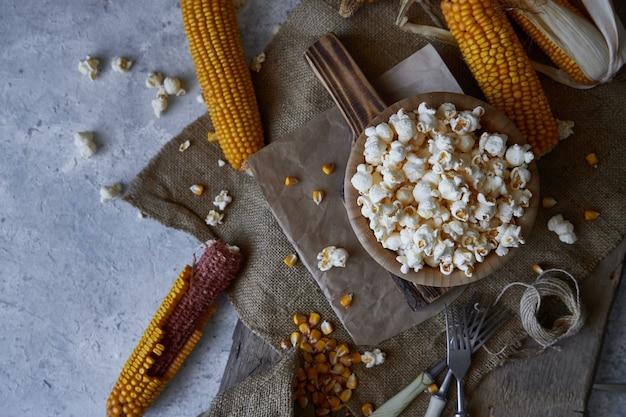 Traditionele popcorn in een houten kom en maïskolven op de tafel.