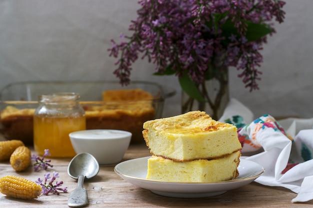 Traditionele roemeense of moldavische cottage cheese braadpan met maïsmeel, geserveerd met honing en zure room.