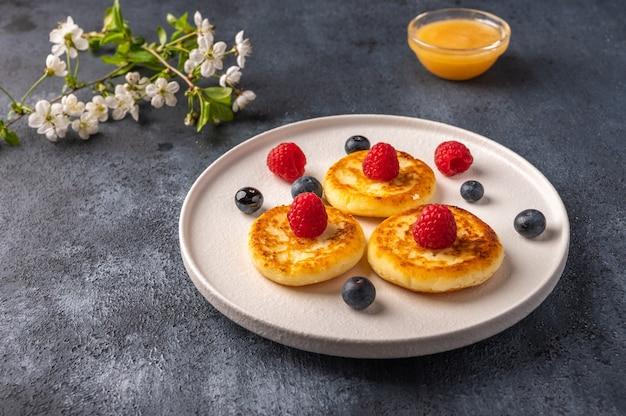 Traditionele russische cheesecake met frambozen, bosbessen en honing op een witte keramische plaat op een donkere achtergrond a