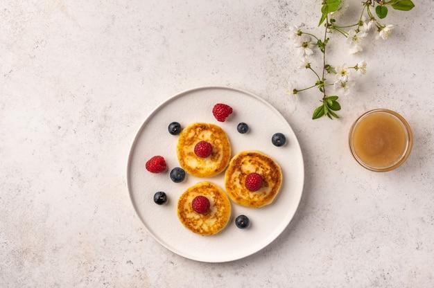 Traditionele russische cheesecake met frambozen, bosbessen en honing op een witte keramische plaat op een lichte achtergrond a