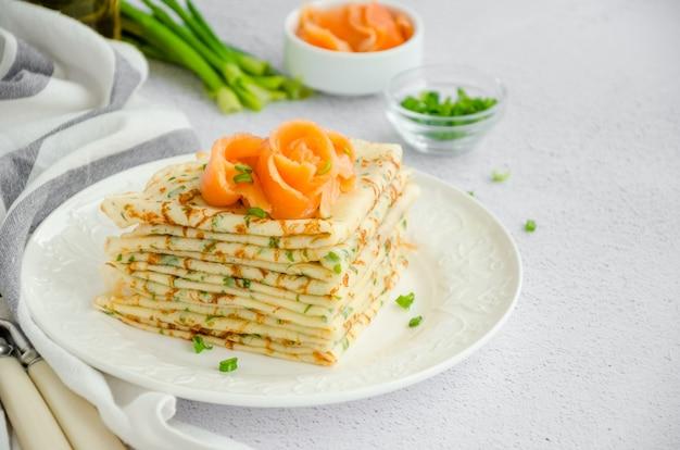 Traditionele russische dunne pannenkoeken of pannenkoeken met kaas, kruiden en gerookte zalm op een witte plaat op een lichte ondergrond vakantie maslenitsa. horizontale oriëntatie