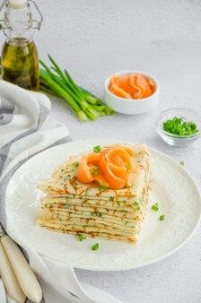 Traditionele russische dunne pannenkoeken of pannenkoeken met kaas, kruiden en gerookte zalm op een witte plaat op een lichte ondergrond vakantie maslenitsa. verticale oriëntatie.