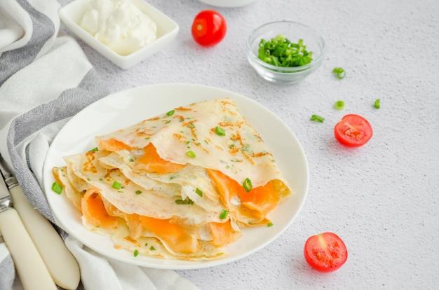 Traditionele russische dunne pannenkoeken of pannenkoeken met roomkaas, gerookte zalm en groene uien op een witte plaat op een lichte ondergrond vakantie maslenitsa. horizontale oriëntatie.