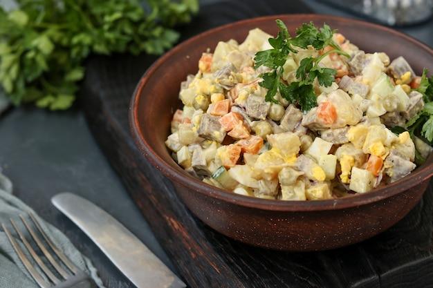 Traditionele russische feestelijke salade olivier met tong in een kom tegen een donkere achtergrond, horizontale oriëntatie