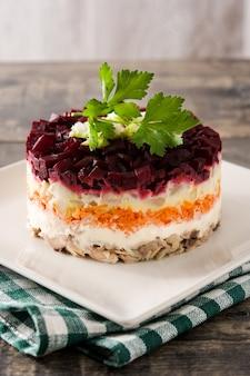 Traditionele russische haring salade met rode biet en wortelen