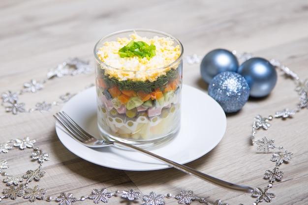 Traditionele russische oliviersalade op een witte plaat in een glas