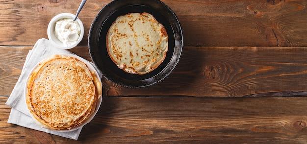 Traditionele russische pannenkoeken blini gestapeld in een plaat en pannenkoek in gietijzeren koekenpan op houten tafel. maslenitsa russische festivalmaaltijd. russische keuken. bovenaanzicht.