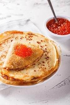 Traditionele russische pannenkoeken blini gestapeld in een plaat met rode kaviaar. maslenitsa traditionele russische festivalmaaltijd. russisch eten, russische keuken