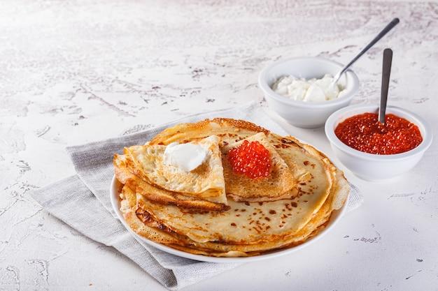 Traditionele russische pannenkoeken blini gestapeld in een plaat met rode kaviaar, verse zure room. maslenitsa traditionele russische festivalmaaltijd. russisch eten, russische keuken