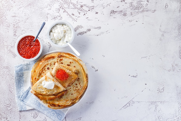 Traditionele russische pannenkoeken blini gestapeld in een plaat met rode kaviaar, verse zure room. maslenitsa traditionele russische festivalmaaltijd. russische keuken. bovenaanzicht.