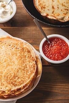 Traditionele russische pannenkoeken blini gestapeld in plaat en gietijzeren koekenpan met rode kaviaar, verse zure room op donkere houten tafel. russische festivalmaaltijd maslenitsa of shrovetide.