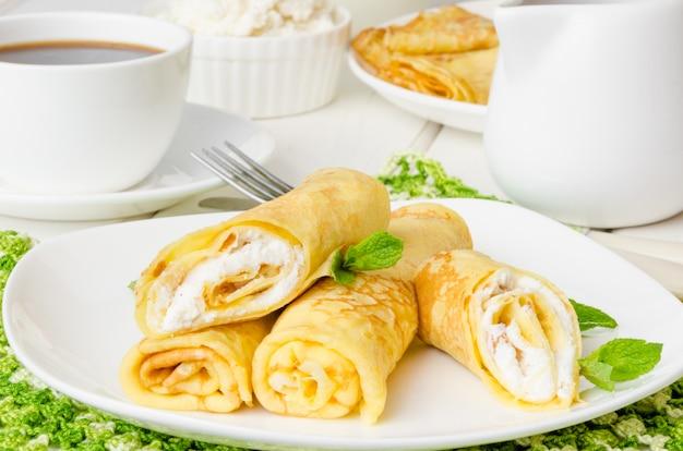 Traditionele russische pannenkoeken met zoete kwark, rozijnen en kersensaus voor het ontbijt