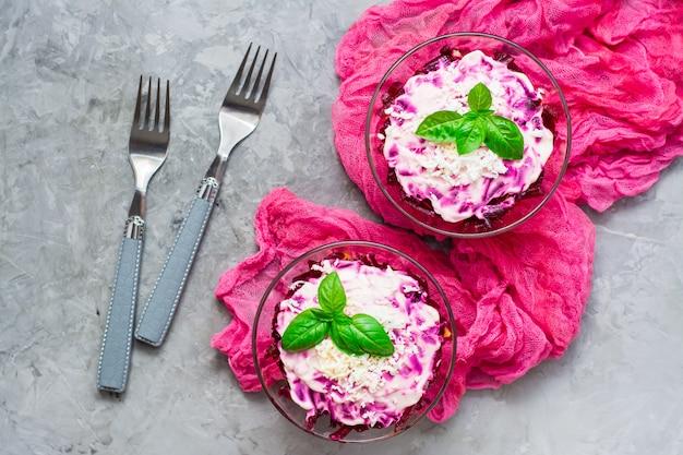 Traditionele russische salade, haring onder een bontjas in kommen en vorken op de tafel. bovenaanzicht