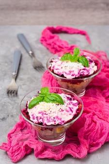 Traditionele russische salade, haring onder een bontjas in kommen op de tafel