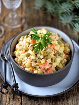 Traditionele russische salade olivier op een oude houten ondergrond. russische keuken.