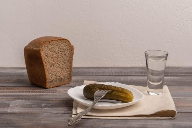 Traditionele russische snack - een glas wodka met augurken en roggezwart brood op linnen servet. ruimte kopiëren.