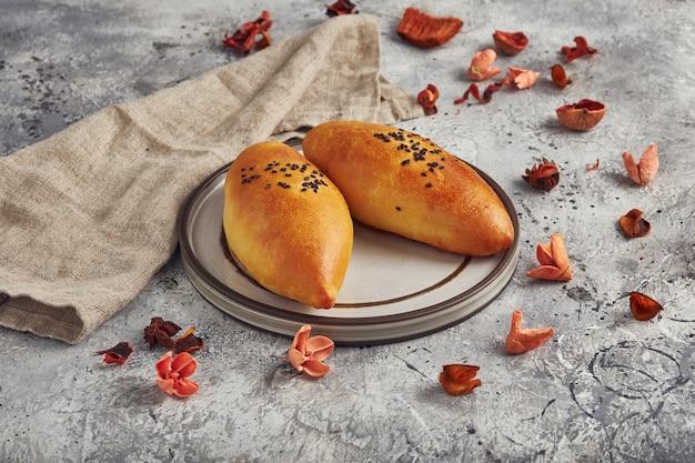 Traditionele russische taarten met groene ui en ei op plaat. russische pirozhki, zelfgemaakte gebakken pasteitjes.