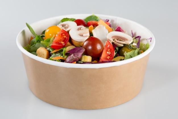 Traditionele salade in een kartonnen container geïsoleerd op een witte