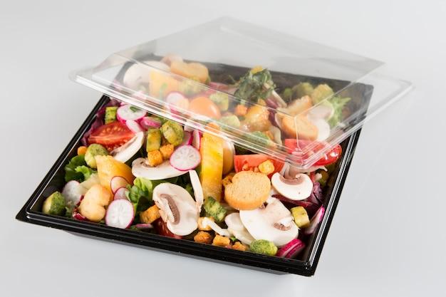 Traditionele salade in zwarte plastic container die op witte achtergrond wordt geïsoleerd