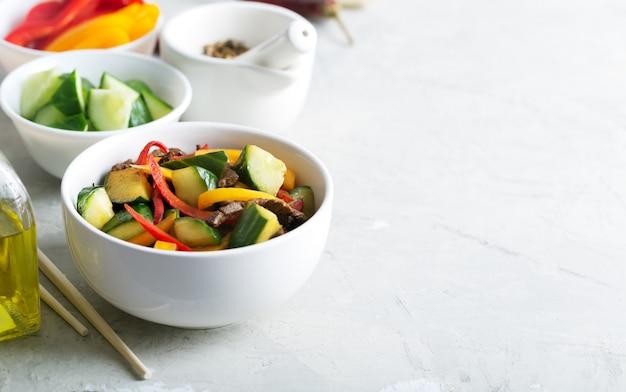 Traditionele salade van uighur-keuken met rundvlees en groenten op de witte lijst
