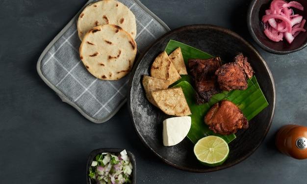 Traditionele salvadoraanse varkenssnack geserveerd met ui en maïstortilla's, latijns-amerika eten