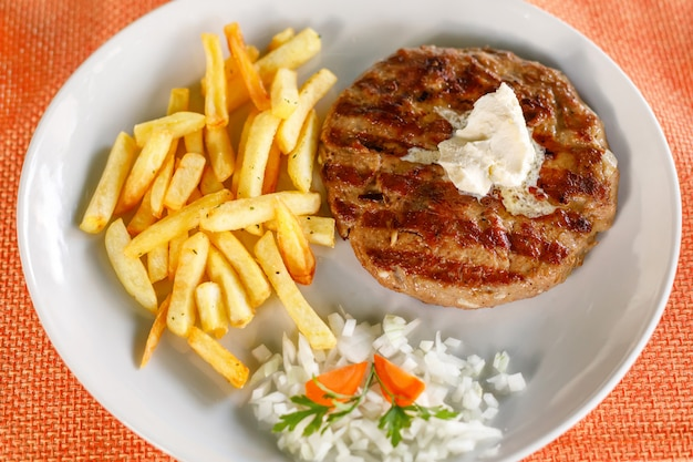Traditionele servische pljeskavica geserveerd met frietjes