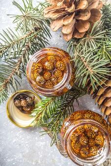 Traditionele siberische en oekraïense zoete dessertjam. homemade pine cone jam in kleine schattige potjes, met dennenappels en takken