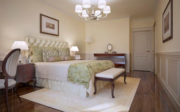 Traditionele slaapkamer in klassieke stijl en logeerkamer met zacht bed in lichte toon met trs getuft hoofdeinde en mahoniehouten meubels en donkerhouten vloeren
