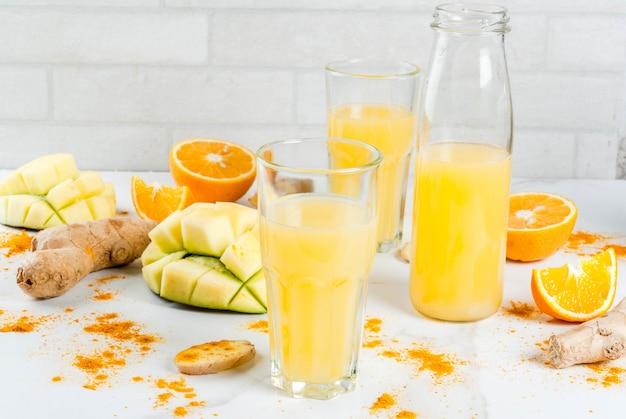 Traditionele smoothie van mango, sinaasappel, kurkuma en gember