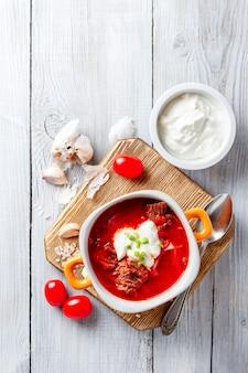 Traditionele soep van russische en oekraïense keukenborsch. vleessoep met bieten in een oranje kom. bovenaanzicht.