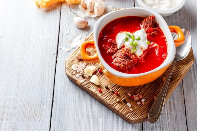 Traditionele soep van russische en oekraïense keukenborsch. vleessoep met bieten in een oranje kom.